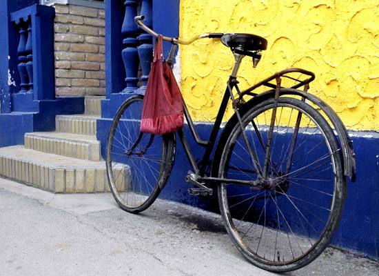 Bicycle leaning against a blue and yellow wall